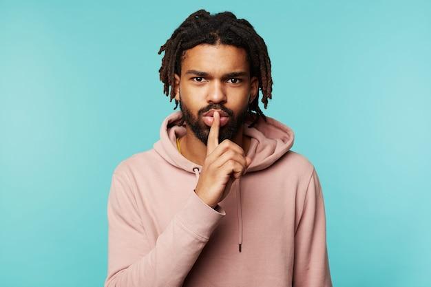 Sérieux jeune homme barbu aux cheveux noirs aux yeux bruns, levant la main avec un geste silencieux à sa bouche tout en demandant de garder le silence, debout sur fond bleu