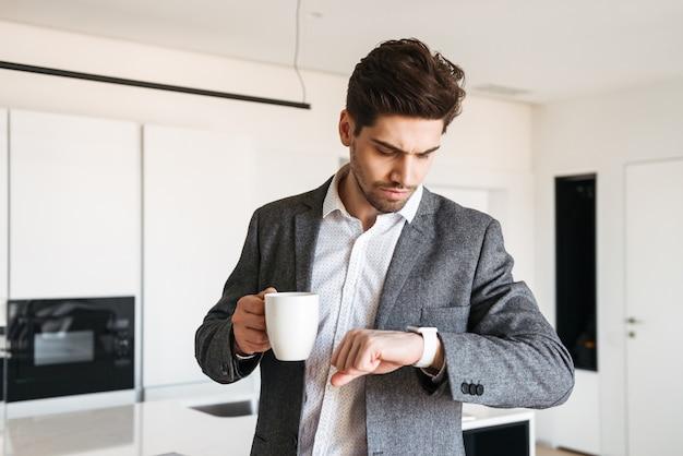 Sérieux jeune homme en costume regardant sa montre-bracelet