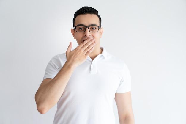Sérieux jeune homme couvrant la bouche avec la main. mec attrayant gêné.