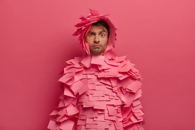 Sérieux, jeune homme européen lève les sourcils, écoute attentivement les informations, se prépare à la fête costumée au bureau, recouvert de notes adhésives, pose contre le mur rose. monochrome