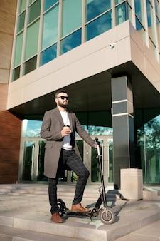 Sérieux jeune homme en pantalon, manteau et lunettes de soleil debout sur un scooter électrique par l'architecture moderne et ayant un verre de café