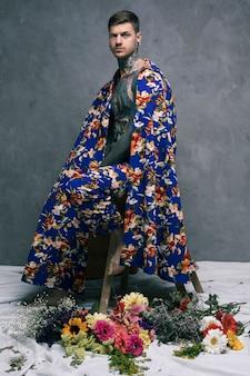 Sérieux jeune homme tatoué dans un drapé floral, regardant la caméra