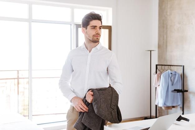 Sérieux jeune homme tenant sa veste