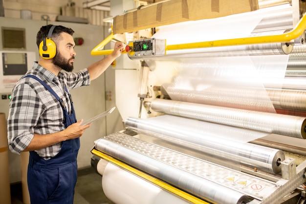 Sérieux jeune ingénieur d'usine de production chimique prenant le contrôle du processus de fabrication d'un film de polyéthylène