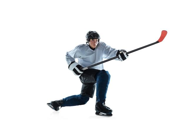 Sérieux. jeune joueur de hockey masculin avec le bâton sur le court de glace et le fond blanc. sportif portant un équipement et un casque pratiquant. concept de sport, mode de vie sain, mouvement, mouvement, action.