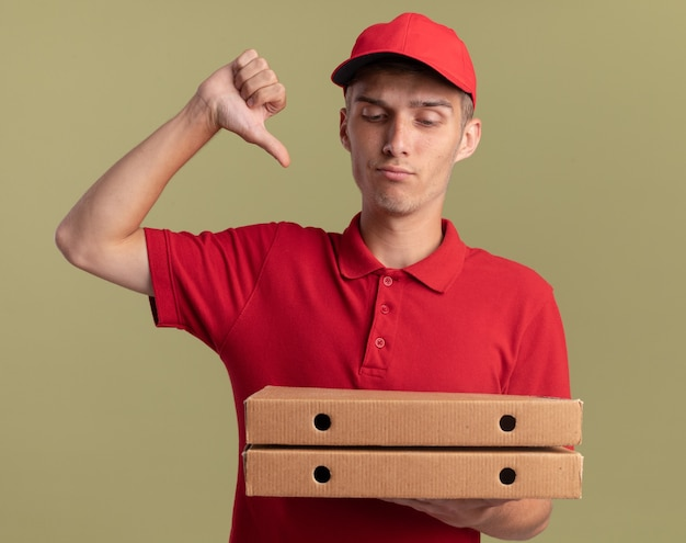 Sérieux jeune livreur blond pouce vers le bas tenant et regardant des boîtes à pizza