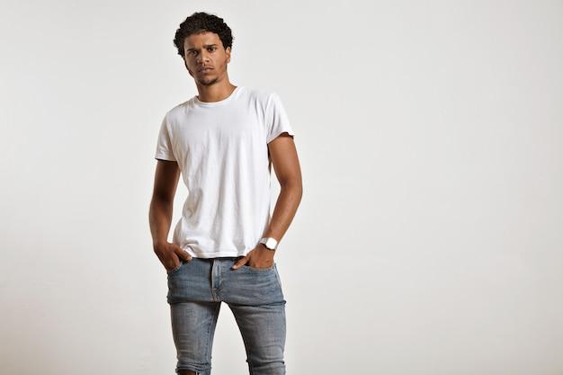 Sérieux jeune mannequin afro-américain athlétique avec les mains dans les poches de son jean bleu serré portant un t-shirt blanc