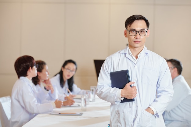 Sérieux jeune pharmacologue métis avec ordinateur tablette debout dans la salle de réunion, ses collègues discutant d'un nouveau vaccin en arrière-plan