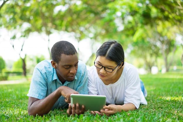 Sérieux jeunes amis étudiants multiethniques à l'aide du pavé tactile
