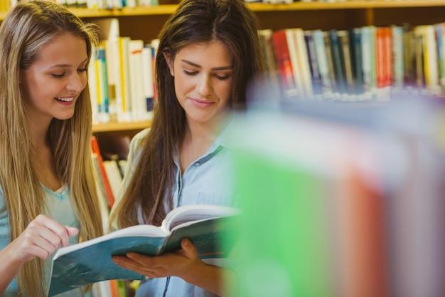 Sérieux jeunes étudiants travaillant ensemble dans la bibliothèque