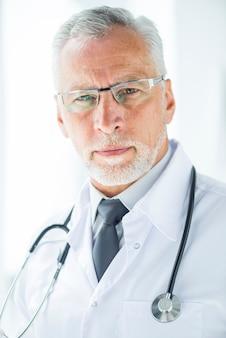 Sérieux médecin senior à lunettes