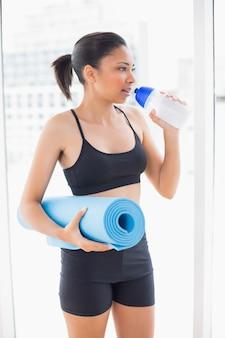 Sérieux modèle aux cheveux foncés en tenue de sport portant un tapis d'exercice et de l'eau potable