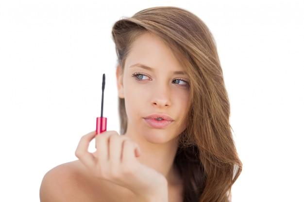 Sérieux modèle brune en regardant un tube de mascara