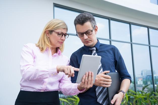 Sérieux partenaires commerciaux examinant quelque chose sur une tablette à l'extérieur.