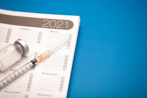 Seringue et bidon de vaccin, avec calendrier 2021, surface bleue