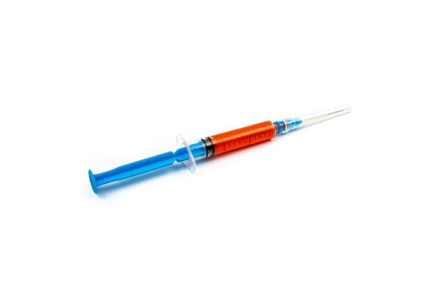 Seringue bleue avec vaccin épidémique de coronavirus rouge sur fond blanc