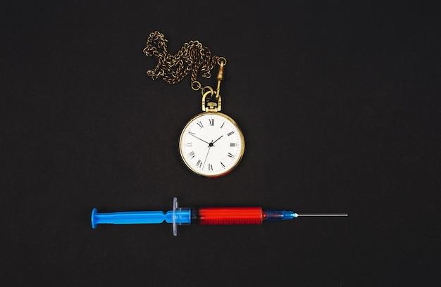 Seringue bleue avec un vaccin rouge contre le coronavirus sur fond noir avec une horloge. problème réel de la lutte contre les virus.