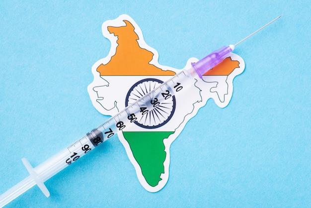 Seringue avec un certain vaccin de traitement médical sur le drapeau de l'inde