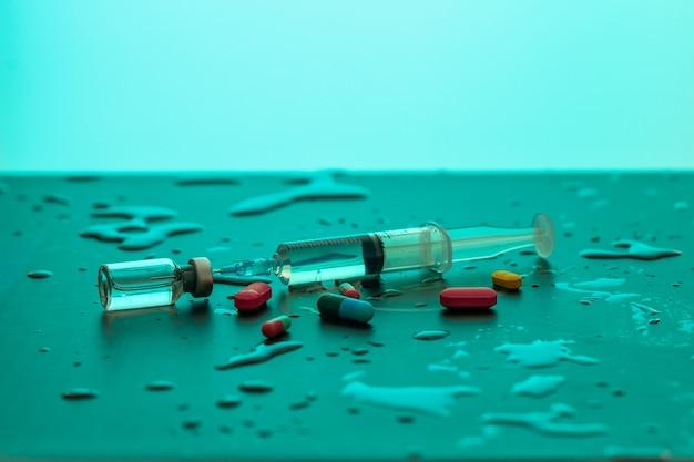 Seringue dactylographiée avec un médicament se trouvant entre des gouttes d'eau et diverses pilules. concept de santé.