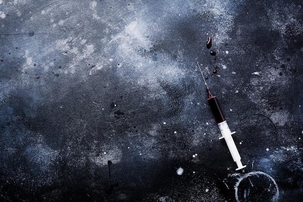 Seringue avec du sang sur la vieille table en béton