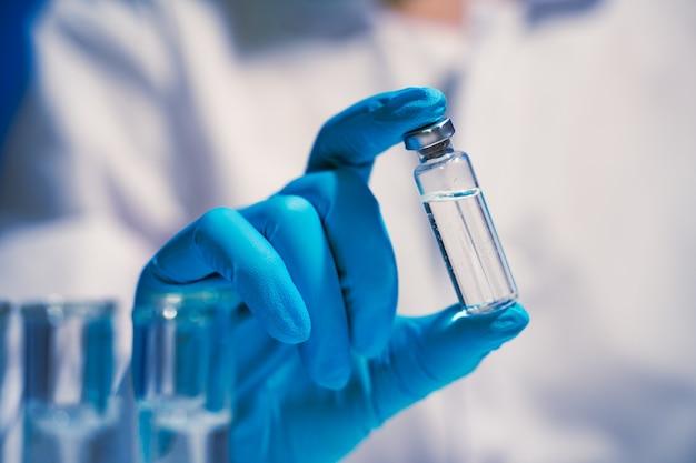 Seringue d'injection de vaccin contre le coronavirus covid-19 entre les mains d'un chercheur en pharmacologie et en vaccin en laboratoire, développement d'un vaccin contre le coronavirus covid-19
