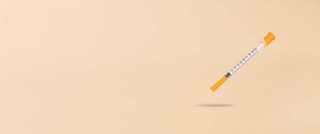 Seringue à insuline à lévitation sur fond beige avec espace de copie.