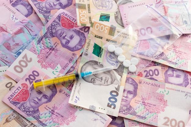 Seringue, pilules dans un sac en plastique à fermeture éclair et beaucoup d'argent ukrainien. vente de médicaments.