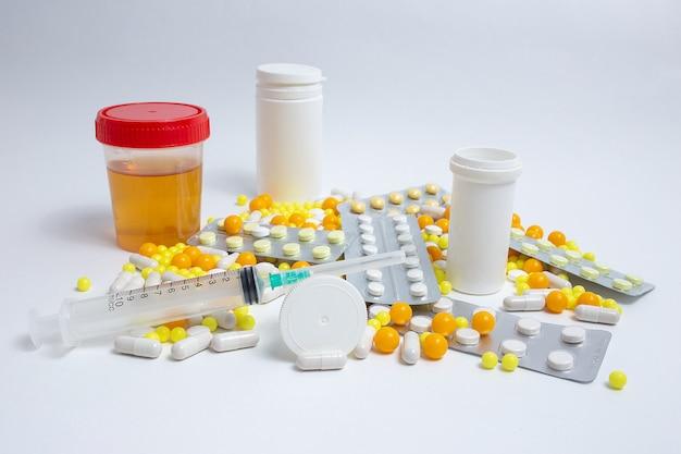 Seringue, pilules médicinales, capsules, flacons, test d'urine sur mur de béton gris