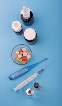 La seringue et les pilules sont sur la table, les fournitures médicales sont sur le tableau bleu