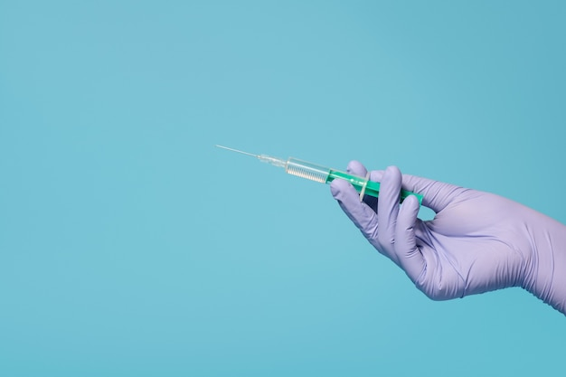 Seringue pour injection de vaccin à la main, gants médicaux en latex à portée de main. sur fond bleu.
