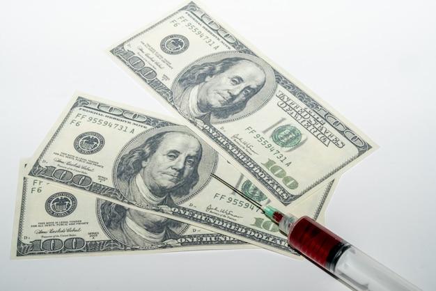 Seringue de sang sur fond blanc avec de l'argent