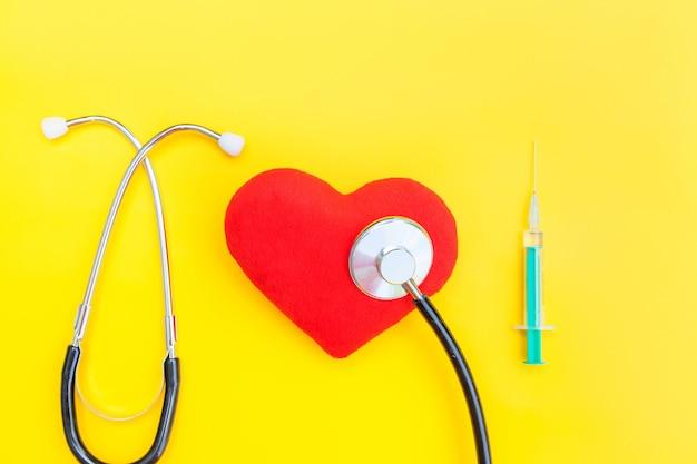 Seringue de stéthoscope de matériel de médecine et coeur rouge isolé sur fond jaune