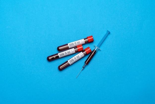 Seringue et tube à essai en plastique avec échantillon de sang sur bleu