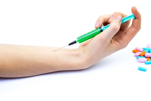 Seringue avec vaccin vert dans la main de la jeune fille sur fond blanc isolé