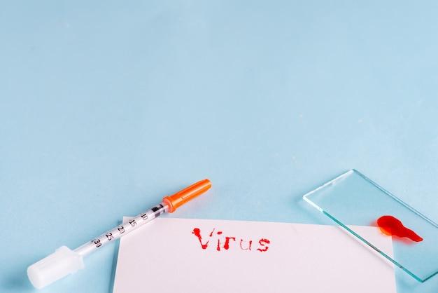 Seringues et tube à essai avec du sang avec du papier blanc et l'inscription virus