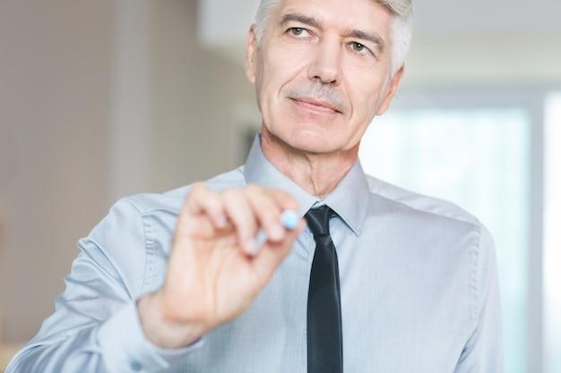 Serious affaires senior réfléchi avec crayon