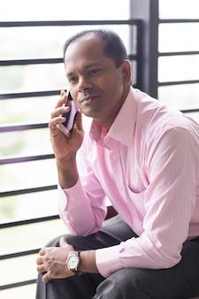 Serious indian business man parlant sur téléphone