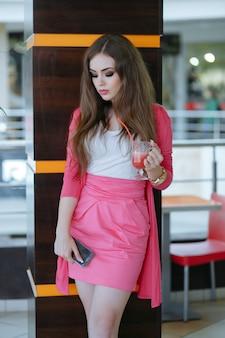 Serious jeune fille avec un soda et un téléphone