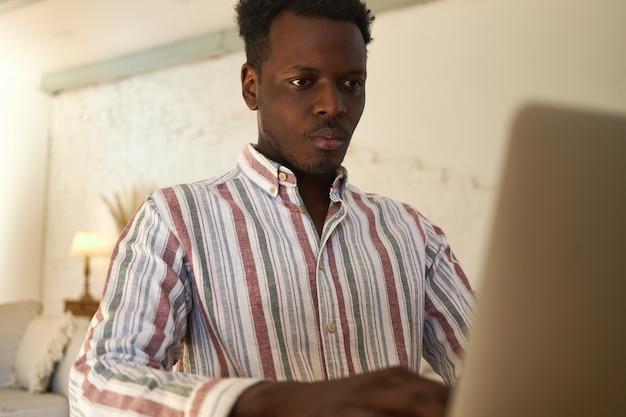 Serious jeune pigiste afro-américain concentré sur un ordinateur portable travaillant à domicile. étudiant ciblé apprenant en ligne à l'aide d'un appareil électronique, test de réussite. technologie, éducation et emploi
