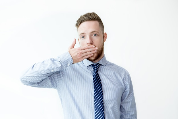 Serious young business man covering mouth