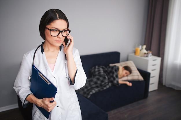 Serius, une jeune femme inquiète, parle au téléphone. elle se tient dans la chambre. son patient allongé sur le canapé derrière. petite fille malade dort.