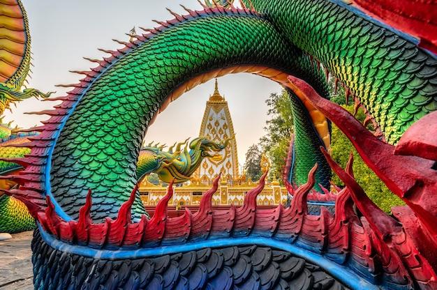 Serpent sculpté en arc-en-ciel ou naga thaïlandais coloré entourant le stupa de sri maha pho chedi au coucher du soleil à wat phra that nong bua, ubon ratchathani