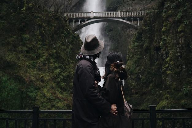 Serrant couple asiatique se tient devant une belle cascade dans les montagnes