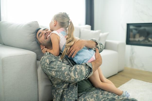 Serrant fort. heureux officier militaire serrant sa jolie fille dans ses bras en rentrant à la maison