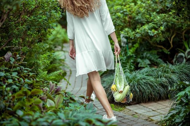 Serre. femme en robe blanche waling et portant des sacs avec différents légumes