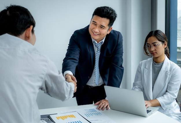Serrer la main après la réunion de l'équipe de femme d'affaires et d'hommes d'affaires pour planifier des stratégies visant à augmenter les revenus de l'entreprise. ayez une analyse graphique de brainstorming et discutez du succès de la nouvelle cible.