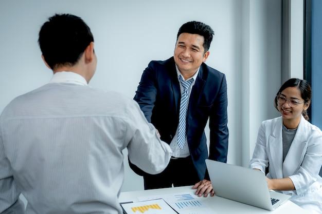 Serrer la main après la réunion de l'équipe de femme d'affaires et d'hommes d'affaires pour planifier des stratégies