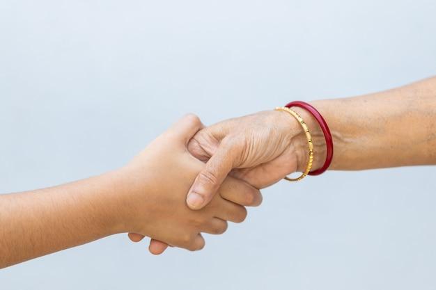 Serrer la main sur un mur gris