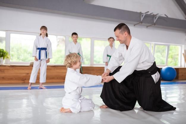 Serrer des mains. rayonnant garçon aux cheveux blonds serrant la main de son entraîneur d'aïkido et souriant