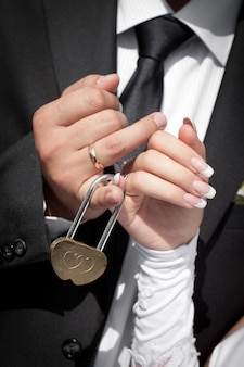 La serrure avec clés en mains du marié et de la mariée